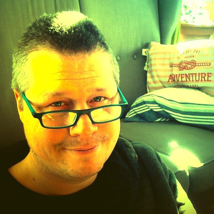Das Bild zeigt den Seitenbetreiber Ralf Bürger, Porträtfoto eines kurzhaarigen Mannes mit Brille, über deren Rand er freundlich in die Kamera schaut.