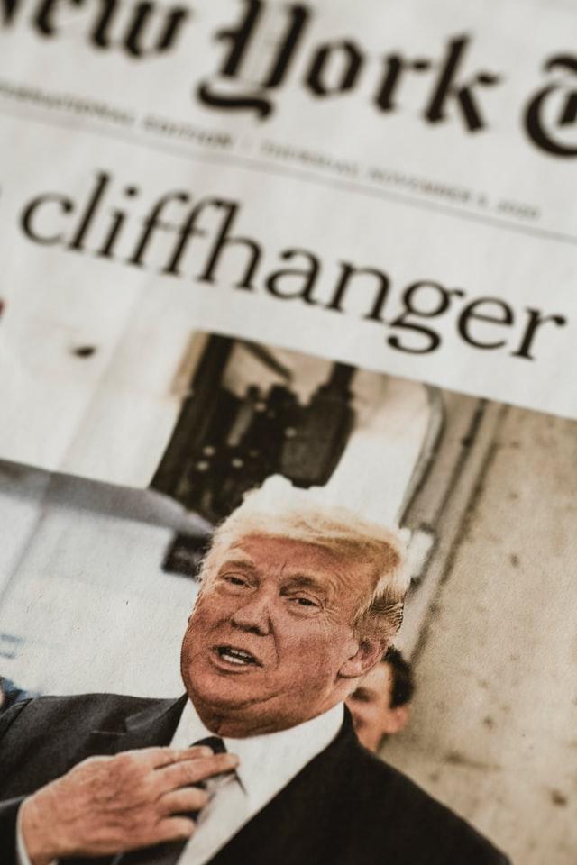 Das Bild zeigt Donald Trump mit halbem Oberkörper, er hat den Mund leicht geöffnet und fasst sich an den Krawattenknoten.