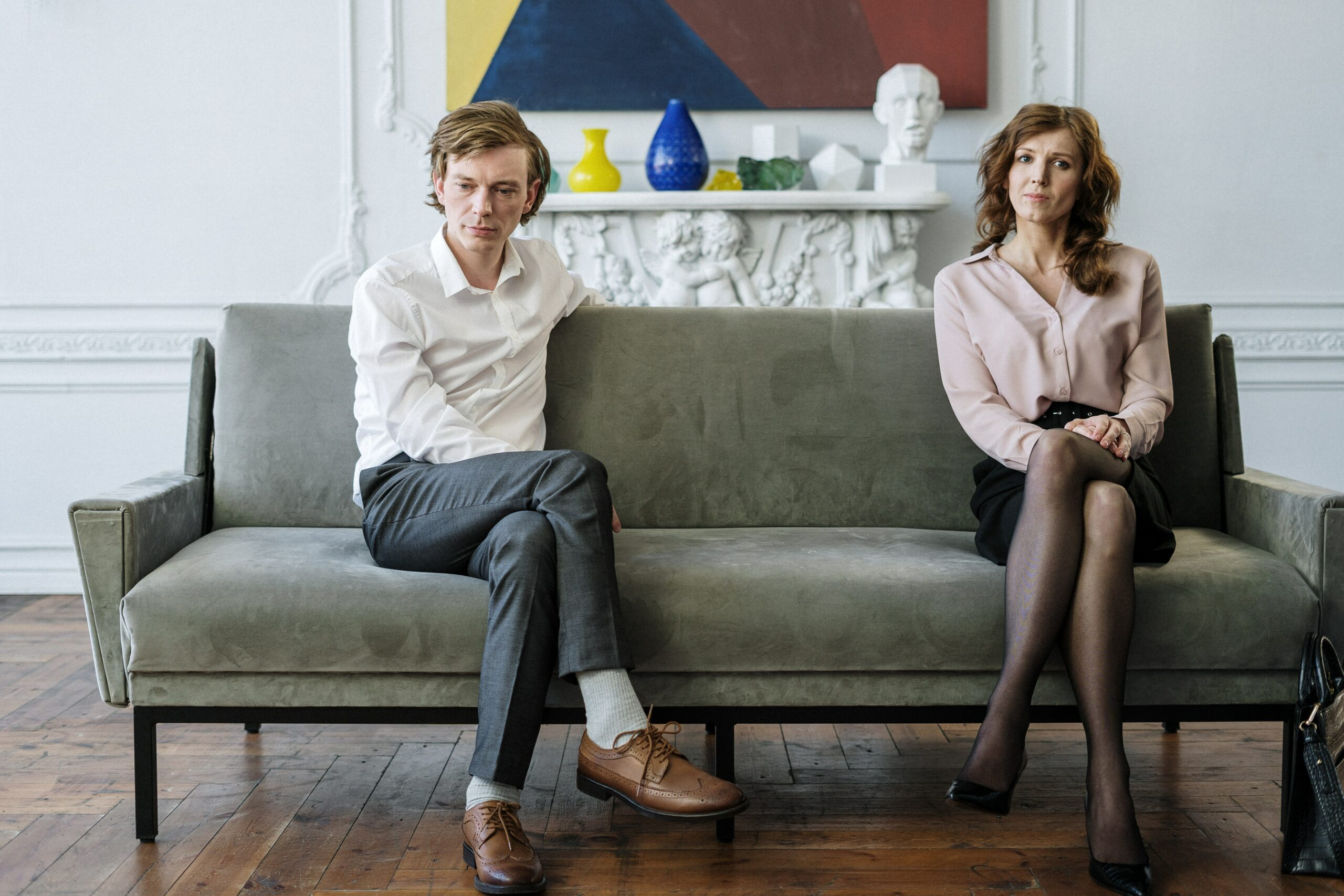Ein Paar, ein Mann und eine Frau, sitzen mit Abstand auf einem Sofa.